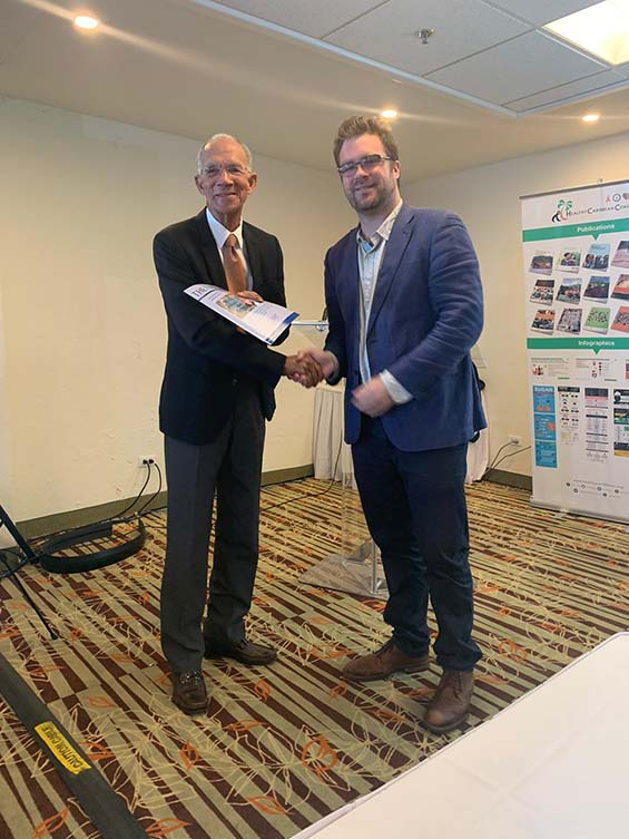 Dr Nick Watts, Executive Director, Lancet Countdown (right) presenting Sir Trevor Hassell with a copy of the Lancet Countdown Report